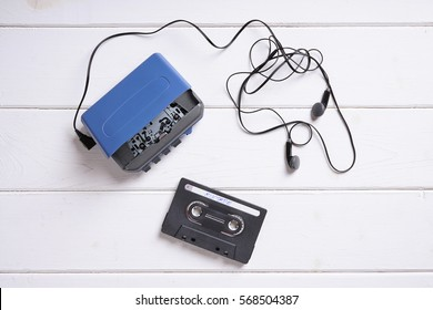 vintage walkman or cassette player with earbuds and mix tape