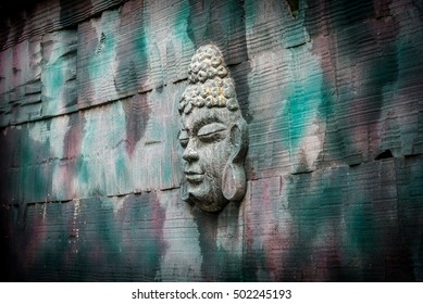 Vintage wall decoration having a buddha face in it