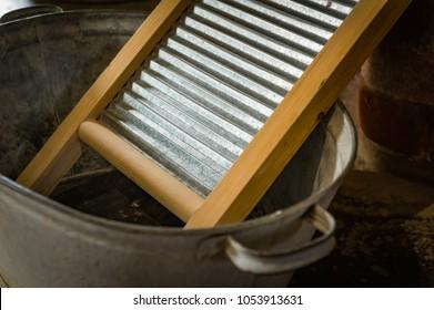 Vintage washboard in an old zinc-coated tin basin.