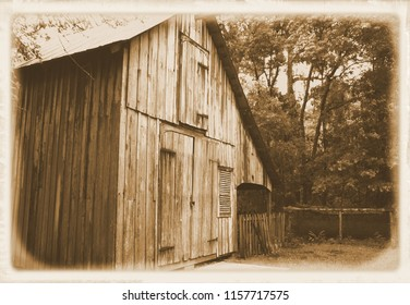 Vintage weathered barn with chicken pen in background old style photograph