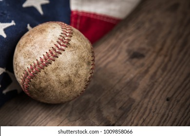 Vintage weathered baseball with vintage American flag on a rustic wooden board