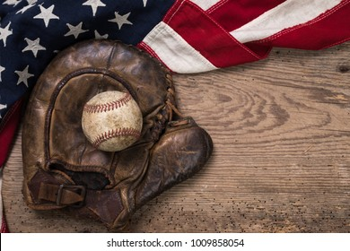 Vintage weathered baseball and glove with vintage American flag on a rustic wooden board