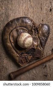 Vintage weathered baseball,glove and bat on a rustic wooden board
