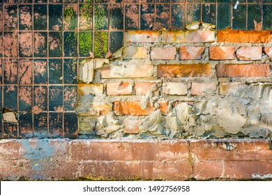 Vintage weathered orange brick wall with remains of cement and plaster, broken layer of old glossy black ceramic vertical tile with spots of red-pink paint