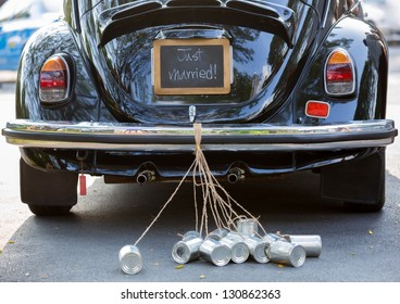 Vintage wedding car with just married sign and cans attached
