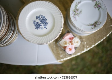 Vintage Wedding Decor Mismatched China on a Table with Flowers and Champagne Gold Sparkly Runner