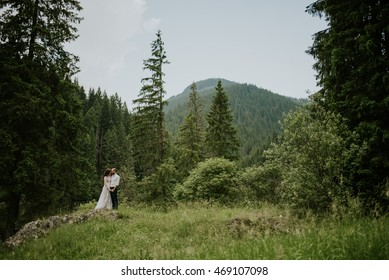Vintage wedding photography of a young hipster couple curly bride posing at sunset in the forest and mountains dressed in a suite and white dress