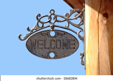A vintage welcome sign on a log structure