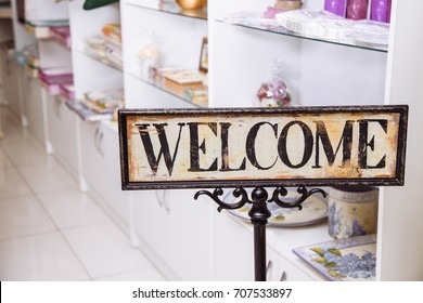 A vintage welcome sign stands at the entrance to the home decor shop