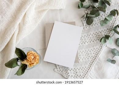 Fondo blanco vintage y postal en blanco - fondo blanco, rosas amarillas, espiral de eucalipto y espacio de copia. Una tarjeta de saludo romántico.