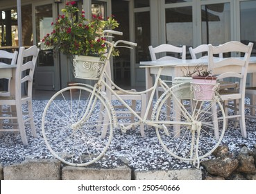 Vintage white bicycle. Cafe tables on background. Greece, Gythio