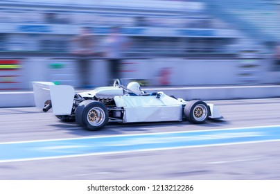 Vintage white formula car driving through pit lane