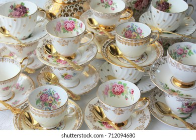Vintage white and stacked tea cups and saucers with gold teaspoons, pink roses, bridal shower high tea party