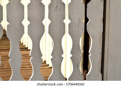 Vintage white veranda. Beautiful decorative boards of the veranda are back-lit with bright sunlight, creating an abstract look.