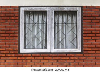 Vintage white window on red brick wall.