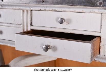 Vintage white wooden desk. Open drawer.
