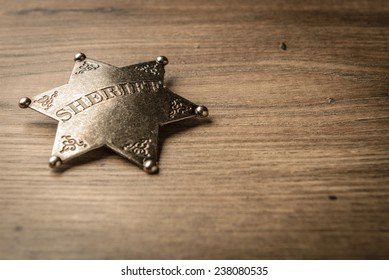 Vintage Wild West Sheriff badge on a rustic wood background.