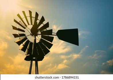 Vintage windmill silhouette against golden glowing morning sun in rural Texas