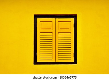 Vintage window with antique yellow shutters isolated on a yellow background wall of traditional Singapore shop house in historic Little India with space for copy