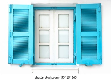 Vintage window with blue shutter on white wall