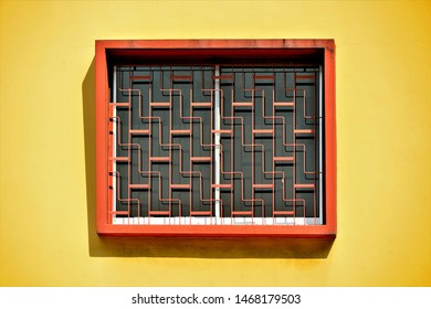 Vintage window with decorative orange metal grill isolated on yellow background wall of traditional Singapore shop house in historic Joo Chiat, East Coast Singapore