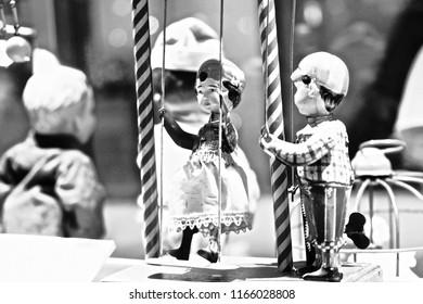 Vintage wind-up toy doll couple enjoying a swing-set