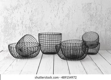 Vintage wire baskets on white wooden rustic floor, industrial wicker storage bins