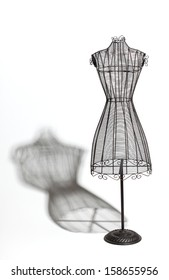 Vintage wire dress form with shadow.