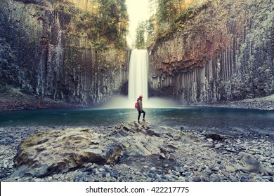 (Vintage) woman on the rock at Abiqua Falls, Oregon. Abiqua Falls is one of the hidden gems in Oregon. Oregon also has many unrecognized falls.  Oregon also has the landscape of old volcanic rocks