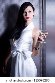 Vintage woman in retro dress with martini on dark background