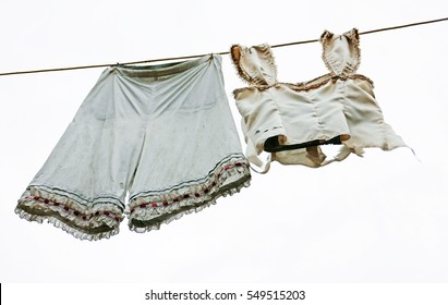 Vintage women's underwear hanging on a clothesline against a bright sky