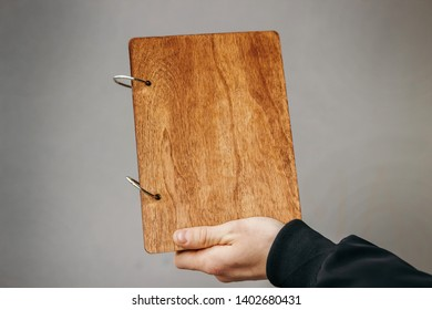 Vintage wood book in female hand. Book on a desk. old wooden book. Photoalbum album. ring mechanism for a wooden book