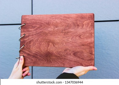 Vintage wood book in female hands. Book on a desk. old wooden book. Photoalbum album