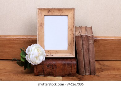 Vintage wood frame with old books on table. Mock up for your photo or text