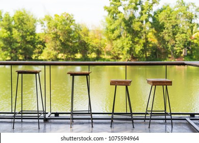 Vintage wood table and chairs on river background, in cafe shop.