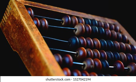 Vintage wooden abacus close up. Counting wooden knuckles. Part of the old end of the abacus on a dark background.