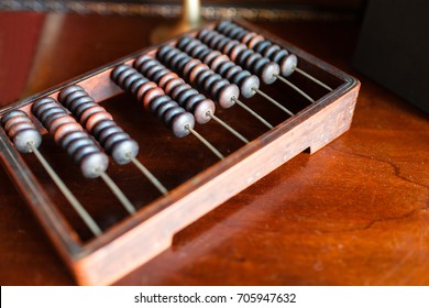 Vintage wooden abacus on a wooden table. The old interpretation of the modern calculator