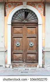 Vintage wooden arched door decorated with floral plaster, moldings and brass door knockers. Volterra. Italy.