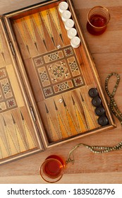 vintage wooden backgammon game on table with rosary and tea