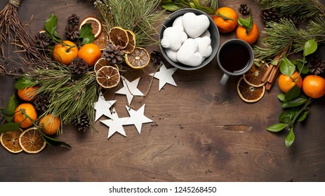 Vintage wooden background with Christmas wreath, fir branches, tangerines, dried orange slices, pine cones and gingerbreads. Top view with copy space