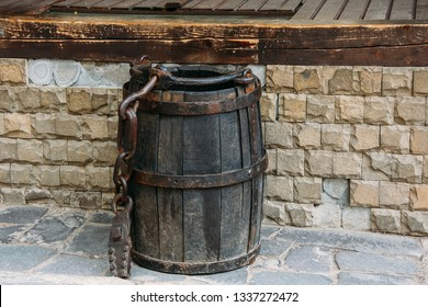 Vintage wooden barrel or bucket with rusty chain and load on wall background