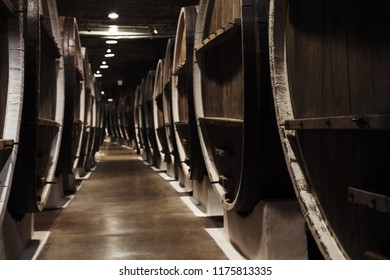 Vintage wooden barrels in winery, retro stylized photo with selective focus