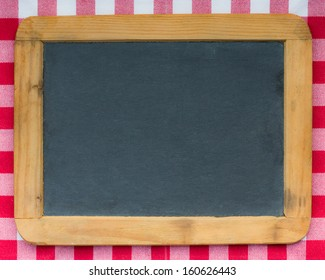 Vintage wooden blackboard on red gingham tablecloth. Copy space for your text