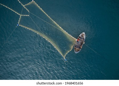Vintage wooden boat in coral sea. Boat drone photo. A fisherman on a fishing boat is casting a net for catching fish.