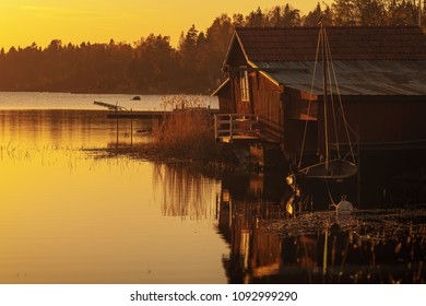 Vintage wooden boat house in red with an old boat anchored beside in a yellow sunlight. Sweden