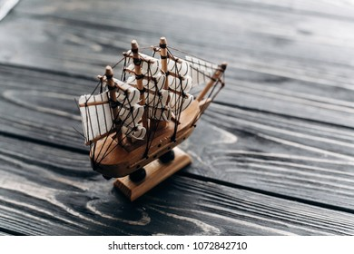Vintage wooden boat toy on wooden background, travel concept, Caravel ship model with sails close-up, pirate concept