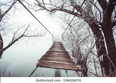 Vintage wooden bridge in the forest during winter time, over the river in Romania, Eastern Europe