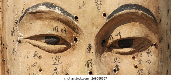 Vintage wooden Buddha face with indicated acupuncture points and names (manual focus on eyes)