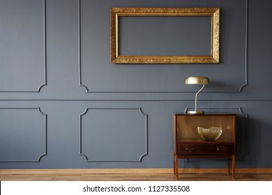 Vintage wooden cabinet and an elegant, empty golden frame on a dark wall with molding in a luxurious living room interior