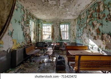 Vintage wooden cafeteria seats reside inside an abandoned hospital.